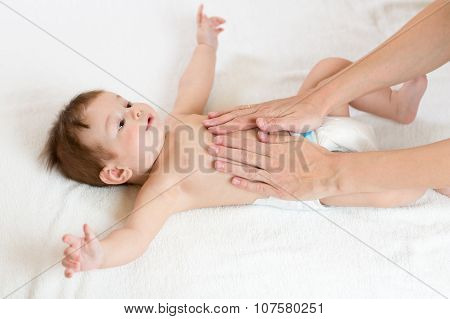 Baby massage. Mother massaging infant belly