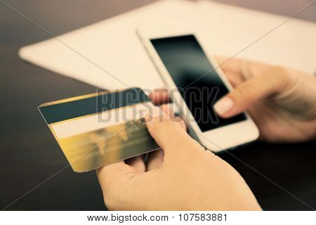 Woman verifies account balance on smart phone with mobile banking application on wooden table background