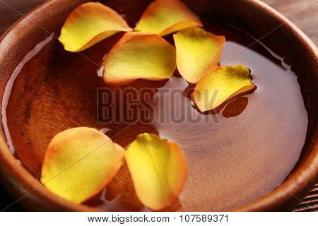 Orange rose petals in a bowl of water, close-up