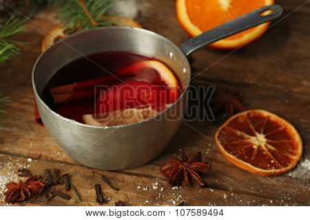 Mulled wine in stew-pan on decorated wooden background