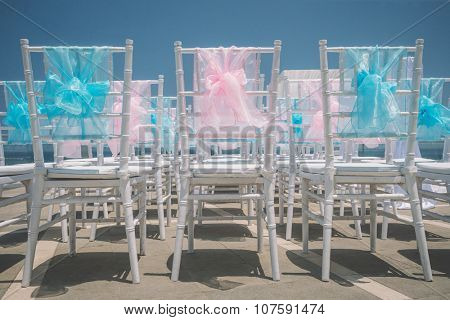 Decorated chairs at dining table on the beach for special guests at a wedding ceremony.