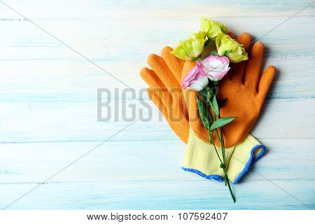 Beautiful composition of flower and garden gloves on light wooden background