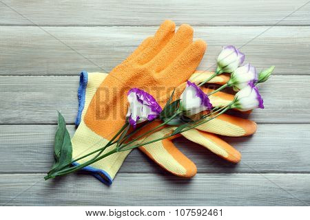 Beautiful composition of flower and garden gloves on grey wooden background