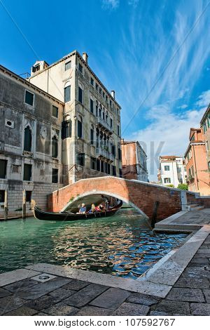VENICE, ITALY - 17 OCTOBER 2015: Gondola passing under a bridge over a small back canal in Venice, Italy as the gondolier takes a group of tourists on a tour of this ancient city. October 17 2015.