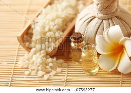 Spa set with massage balls, salt, aroma oil and frangipani flower on wicker background