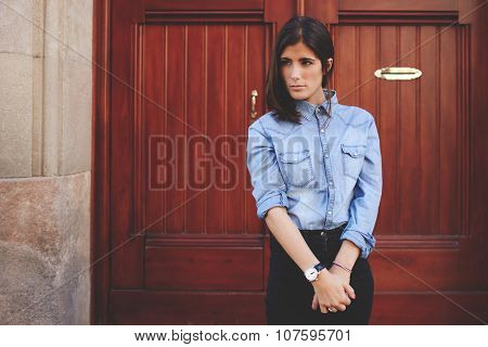 Trendy look of amazing female model on the background of ancient door