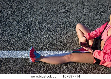 Fit woman using cell telephone while resting after training