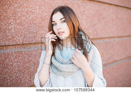 Beautiful Girl In A Sweater Stands Near The Wall