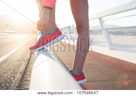 Sporty girl tying the laces on running shoes while taking break between training outside