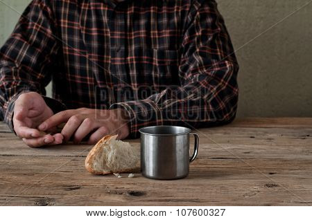 Iron Cup Of Water With A Piece Of Bread