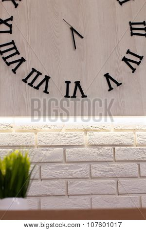 Wooden Clock With Roman Numerals On A White Brick Wall