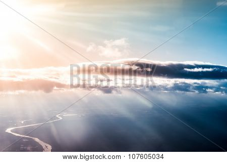 Landscape with clouds and bright sun's rays, curved river below