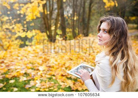 Girl With Tablet In Fall