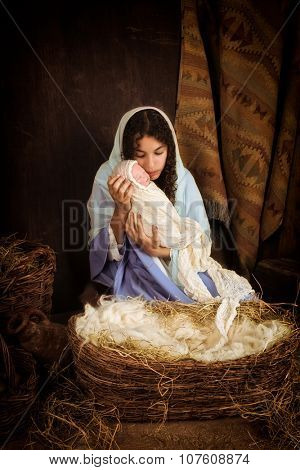 Teenager girl playing the role of the Virgin Mary with a doll in a live Christmas nativity scene  (baby is a doll)