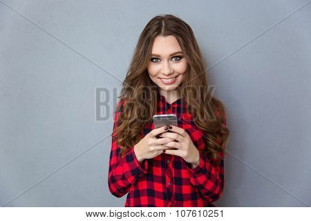 Portrait of a happy teenager girl using smartphone over gray background and looking at camera