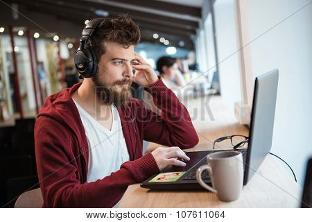 Handsome serious boy with beard in brown hoodie using laptop and listening to music