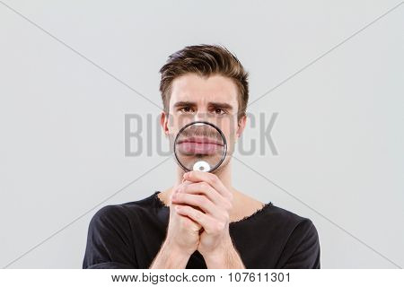 Funny handsome positive man playing tricks using magnifying glass