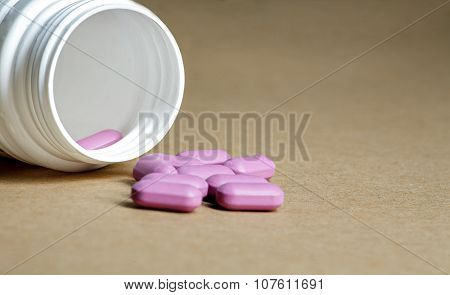 Pink pills spilled from a bottle on a craft paper background