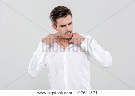Charming attractive young man adjusting his white shirt