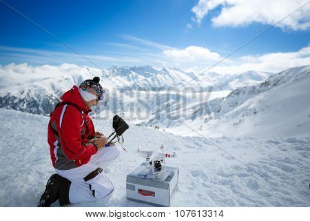 Expert male engineer with remote controls quadrocopter drone a the mountains
