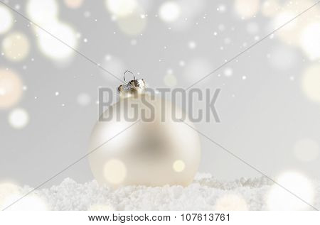 white decorative christmas ball on snow against grey festive background