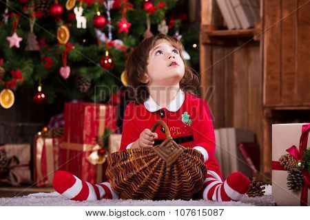Cute little Santa girl dreaming near the Christmas tree, making a wish. Happy new year atmosphere