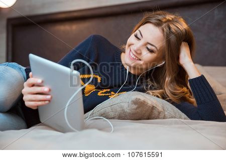 Happy beautiful girl in earphones lying on big bed using tablet