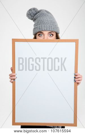 Portrait of a young woman in hat peeping over blank board isolated on a white background