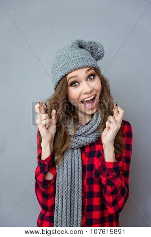 Amusing beautiful funny girl in knitted gray scarf and hat smiling and crossed fingers