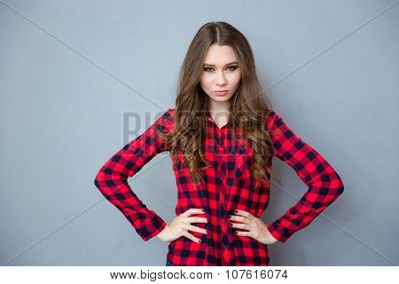 Angry young beautiful curly woman in checkered shirt c standing with arms akimbo