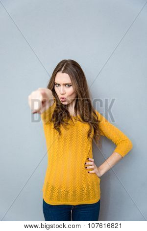 Portrait of a young woman pointing finger at camera over gray background