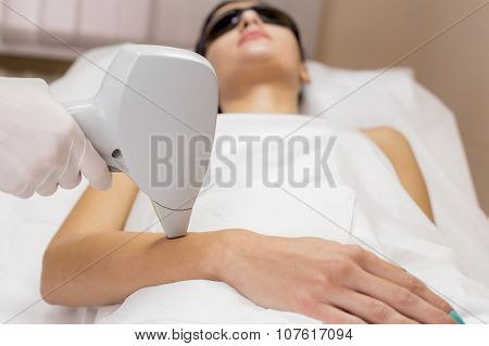 Laser hair removal on client hand in beauty salon
