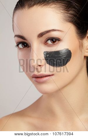 Portrait of girl with black clay smear on the cheek
