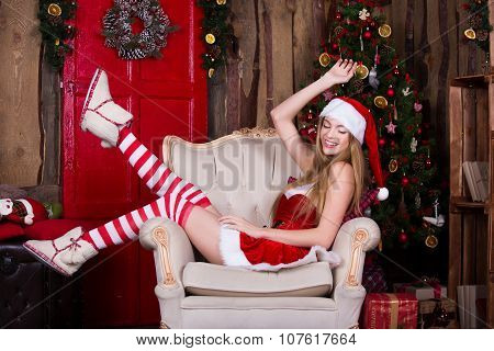 Beautiful Santa girl having fun and smiling near the Christmas tree, sitting in vintage chair. New y