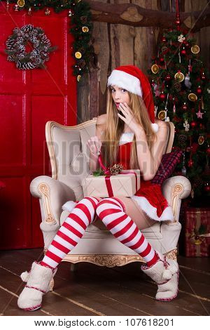 Cute teen girl getting a present near the Christmas tree sitting in chair. New year surprise. Waitin