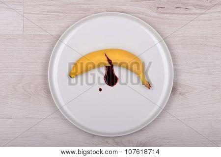 Bleeding Banana On White Plate. Top View. Concept.
