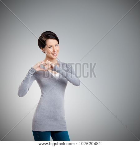 Making a heart hand gesture, isolated on grey