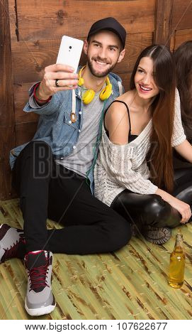Happy friends making selfies while sitting on the floor