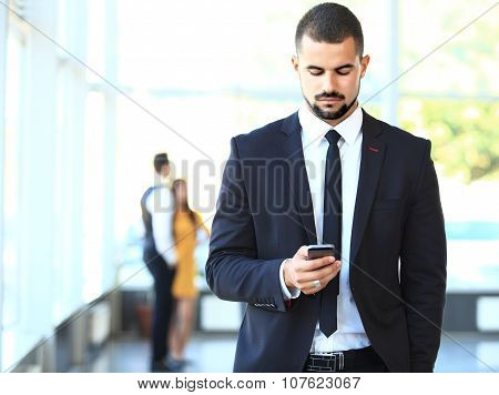 Young Businessman Standing In Office Lobby, Using Smartphone, Smiling.