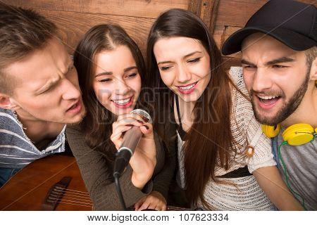Happy friends spending their free time singing karaoke