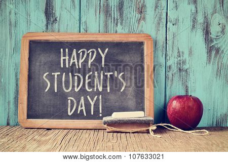 the text happy students day written in a chalkboard, placed on a rustic wooden school desk next to an eraser and a red apple