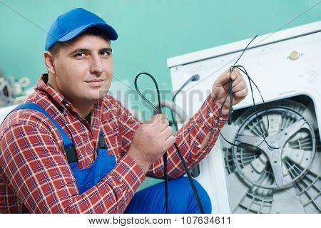 Washing machine repair. Mechanic repairer replacing rubber drive belt