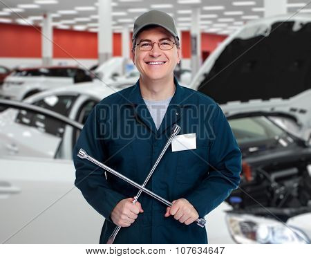 Auto mechanic with tire wrench in garage. Car repair service.
