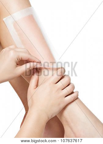 woman depilate her legs by waxing -  studio on white background