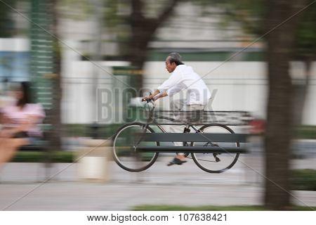 Panning shot on street unknown biker in motion blur