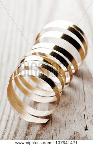 Curly golden ribbon on wooden background macro close-up