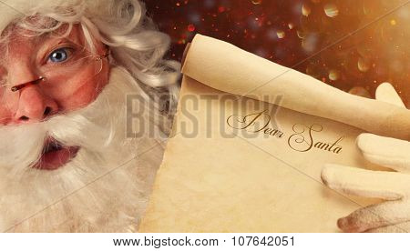 Closeup of Santa Claus holding a Dear Santa scroll