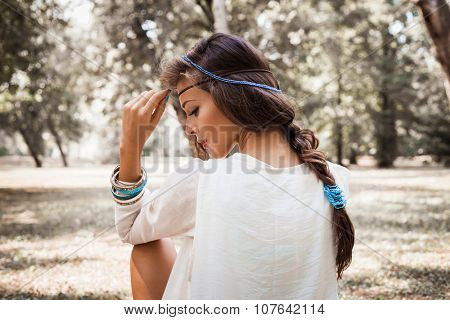 young beautiful woman portrait  in white dress and blue beads in hair, profile, outdoor summer day in forest