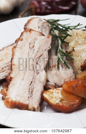 Slices of roasted pork belly or bacon with potato and sauerkraut