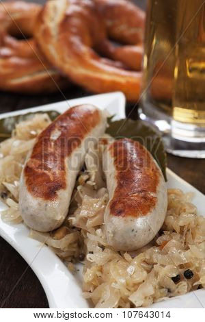 Grilled german white sausage with suaerkraut or sour cabbage and pretzel